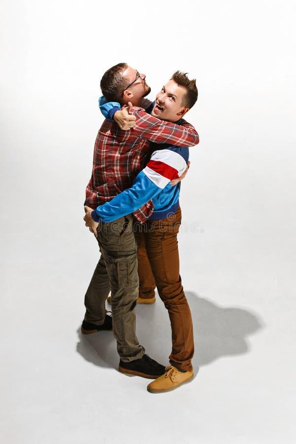 Dos amigos en el desgaste colorido casual que se une y que ríe foto de archivo libre de regalías