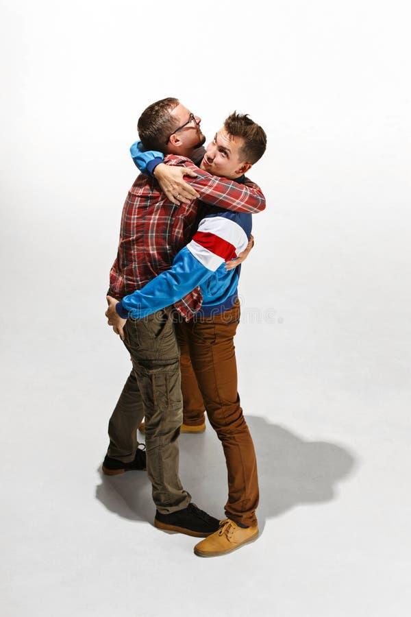 Dos amigos en el desgaste colorido casual que se une y que ríe fotografía de archivo libre de regalías