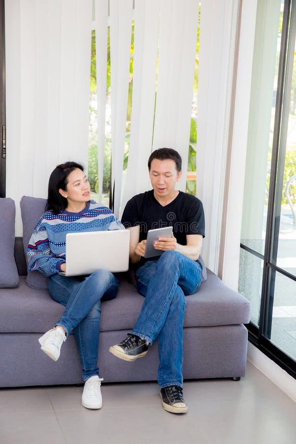 Dos amigos en línea con los dispositivos múltiples y sentarse que habla en un sofá en la sala de estar fotografía de archivo libre de regalías