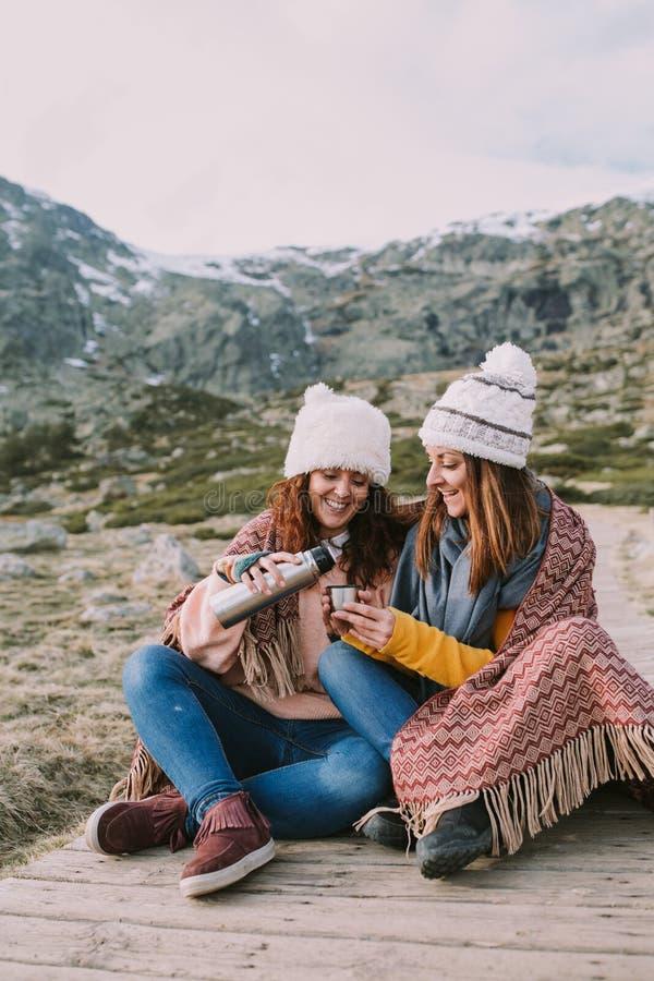 Dos amigos envueltos en una manta se están sentando en el prado mientras que sacan un termo para preparar un caldo foto de archivo libre de regalías