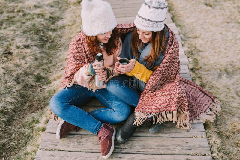 Dos amigos envueltos en una manta se están sentando en el prado mientras que sacan un termo para preparar un caldo imagen de archivo libre de regalías