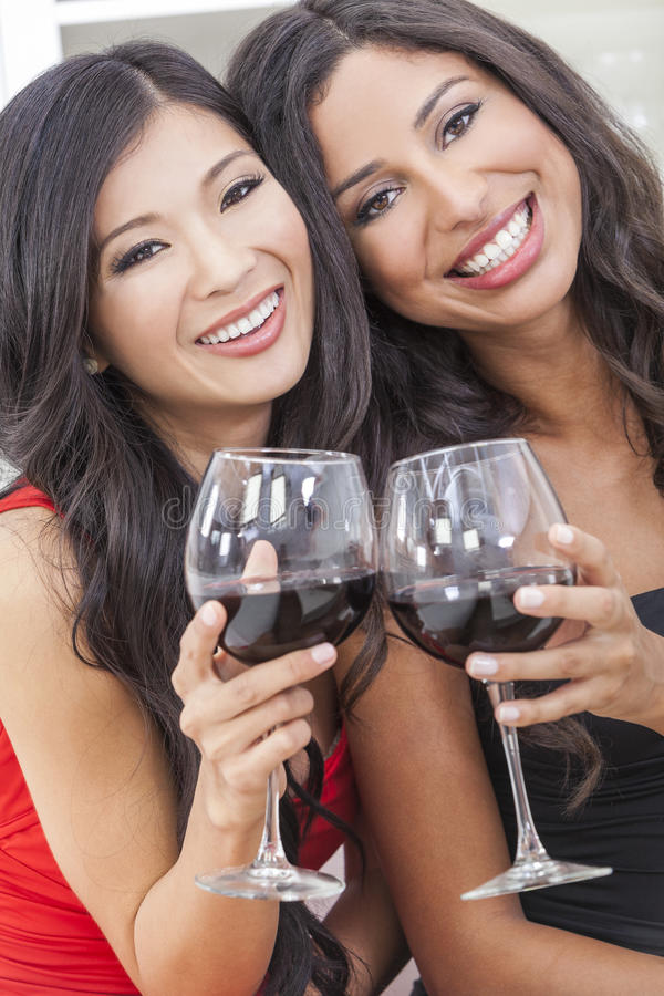Dos amigos felices de las mujeres que beben el vino junto imagen de archivo