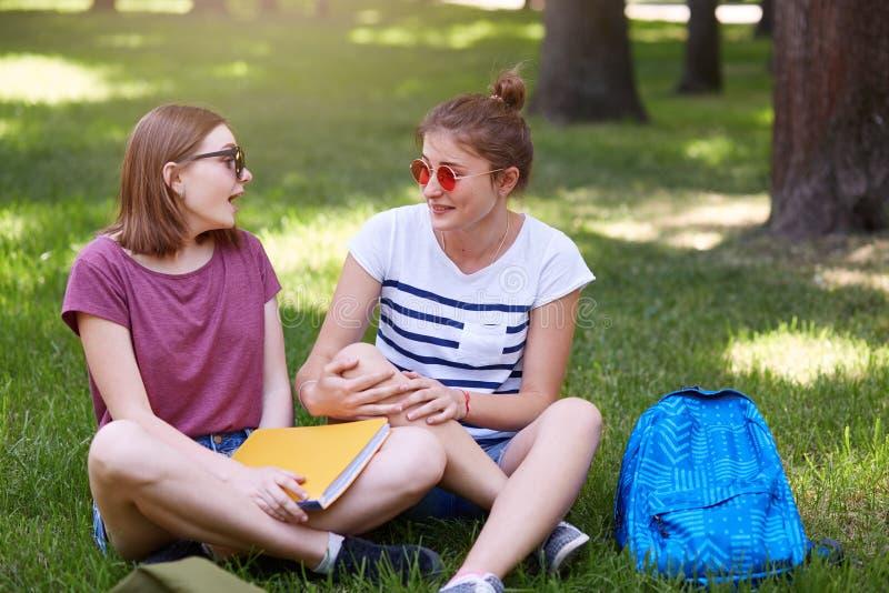Dos amigos felices de los estudiantes que ríen juntos en parque con el fondo verde, se sientan en la posición de loto, llevan la  fotos de archivo