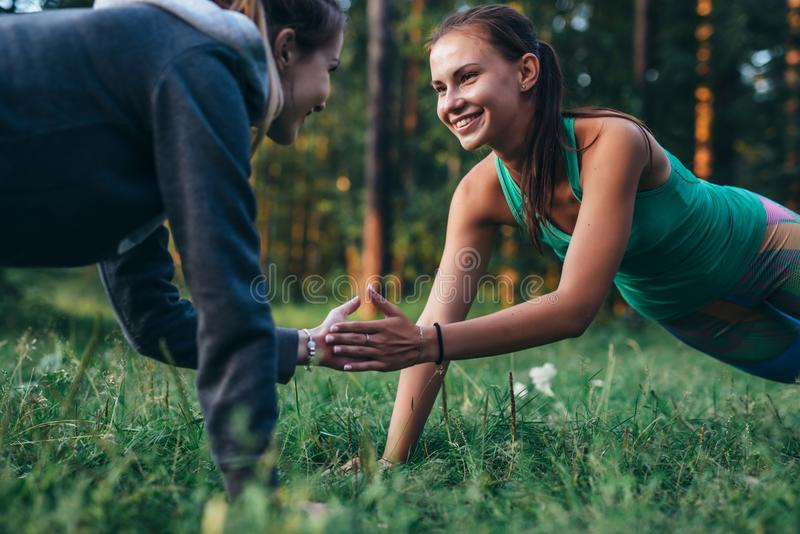 Dos amigos felices que llevan a cabo las manos mientras que hace ejercicio del tablón en parque imagen de archivo libre de regalías
