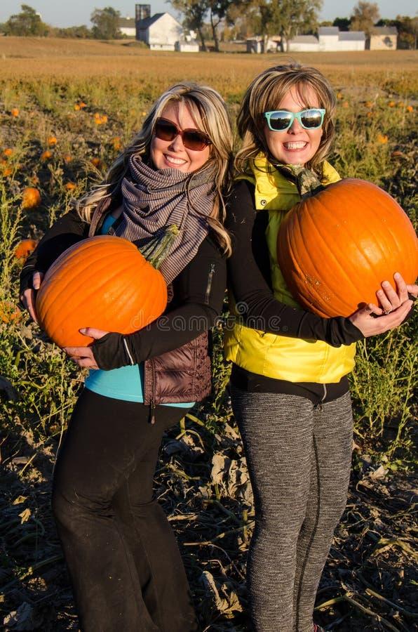 Dos amigos femeninos adultos sostienen las calabazas gigantes en un remiendo de la calabaza imagen de archivo libre de regalías