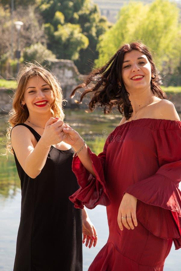 Dos amigos femeninos bailan feliz al aire libre a lo largo de las orillas de un lago foto de archivo libre de regalías