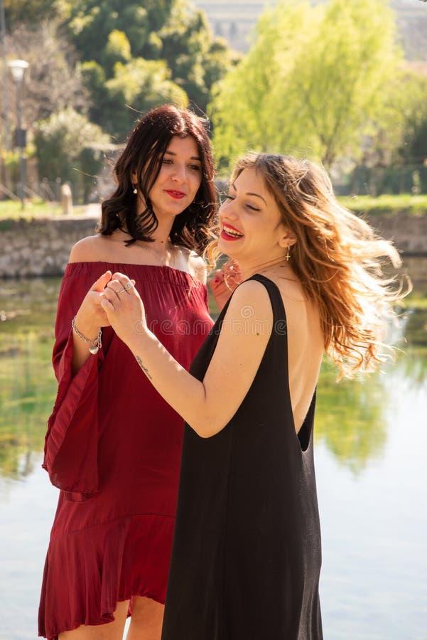 Dos amigos femeninos bailan feliz al aire libre a lo largo de las orillas de un lago fotos de archivo libres de regalías