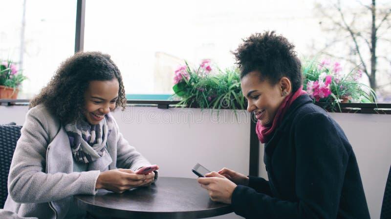 Dos amigos femeninos de la raza mixta atractiva que comparten junto usando smartphone en café de la calle al aire libre fotografía de archivo libre de regalías