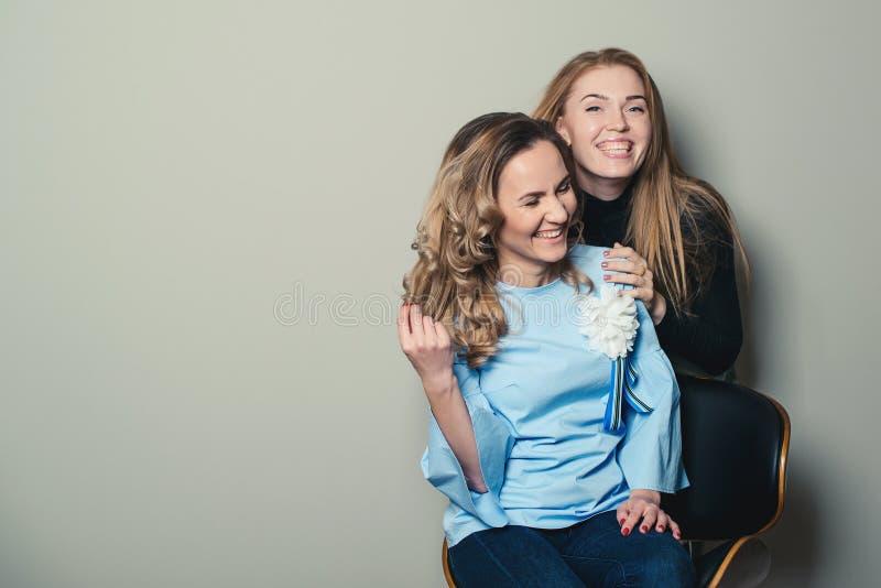 Dos amigos femeninos de risa, aislados en backround gris Copie el espacio Manera de las mujeres Amistad, forma de vida, gente y m imagenes de archivo