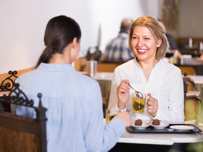 Dos amigos femeninos en la tabla del café fotografía de archivo