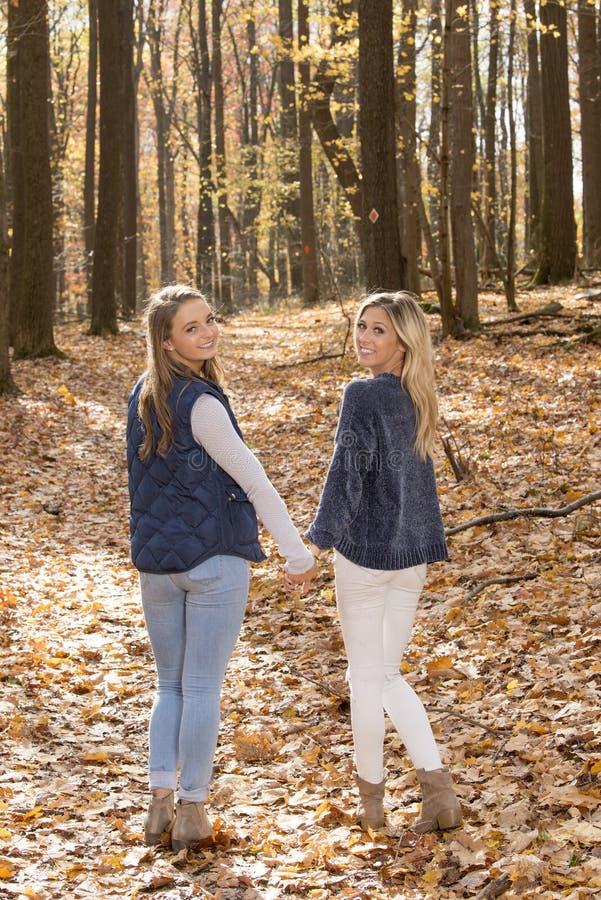 Dos amigos femeninos hermosos caminan en el bosque - otoño imagenes de archivo