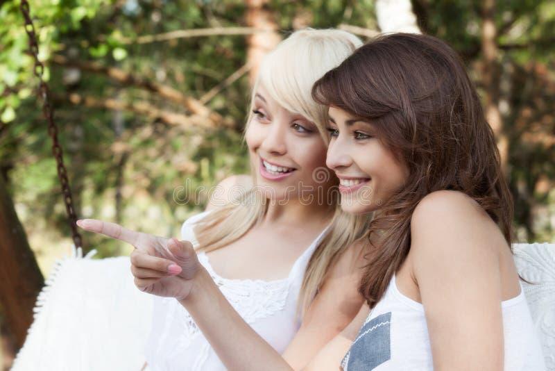 Dos amigos femeninos hermosos que descansan sobre el oscilación y hablar imagenes de archivo
