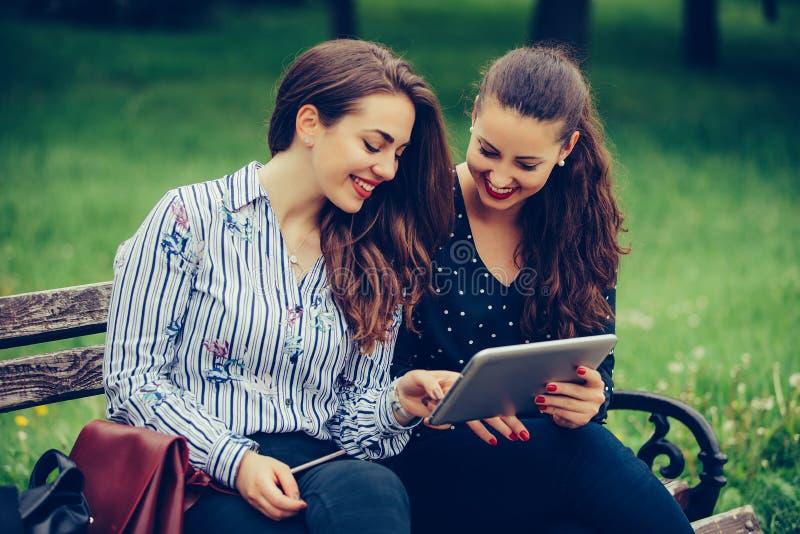 Dos amigos femeninos hermosos que usan una PC y una risa digitales de la tableta foto de archivo libre de regalías
