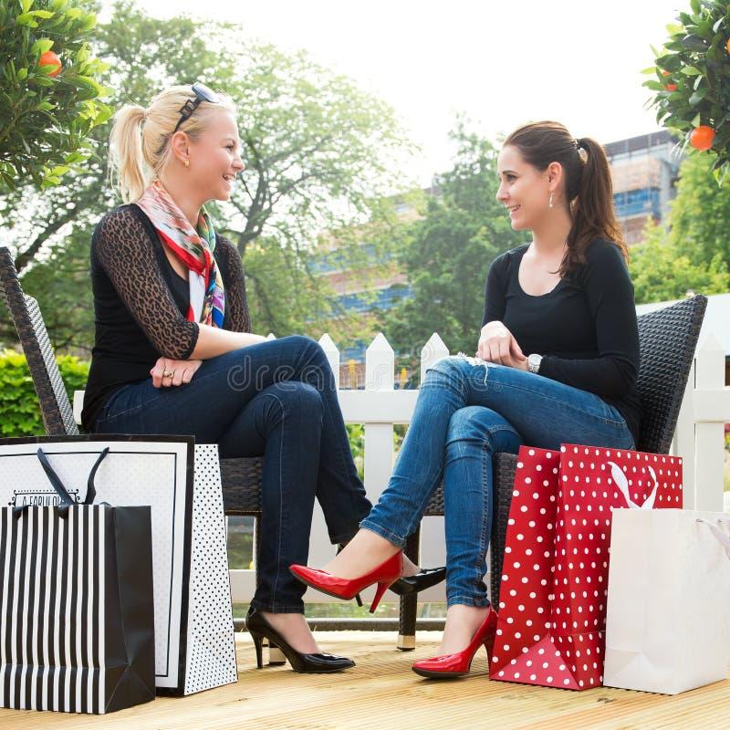 Dos amigos femeninos jovenes atractivos que disfrutan de un día hacia fuera después de compras acertadas fotografía de archivo
