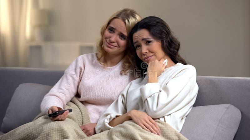Dos amigos femeninos jovenes que miran la telenovela en casa y que lloran, extremo feliz foto de archivo libre de regalías