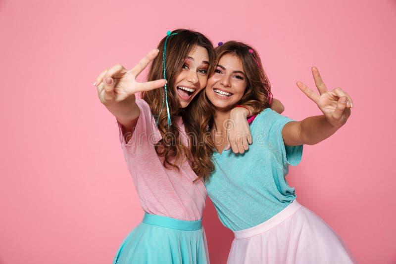 Dos amigos femeninos que abrazan y que se divierten junto, mostrando el peac fotos de archivo libres de regalías