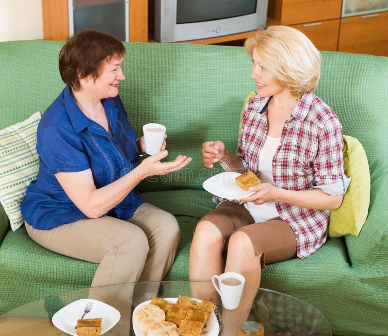 Dos amigos femeninos que beben té foto de archivo