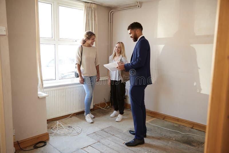 Dos amigos femeninos que compran la casa por la primera vez que mira encuesta sobre la casa con agente inmobiliario fotos de archivo libres de regalías