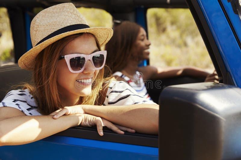 Dos amigos femeninos que conducen el coche de tragante abierto en la carretera nacional foto de archivo libre de regalías