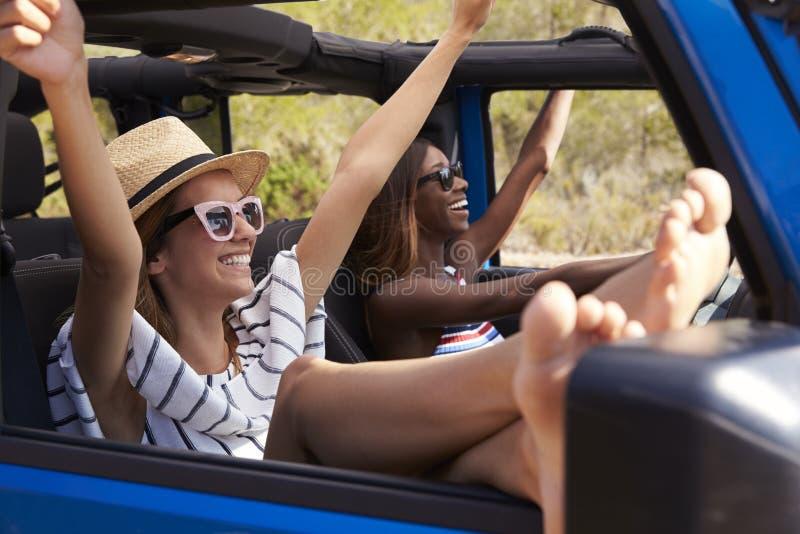 Dos amigos femeninos que conducen el coche de tragante abierto en la carretera nacional imagenes de archivo