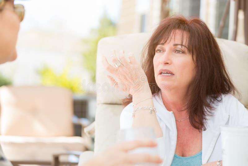 Dos amigos femeninos que disfrutan de la conversación afuera foto de archivo