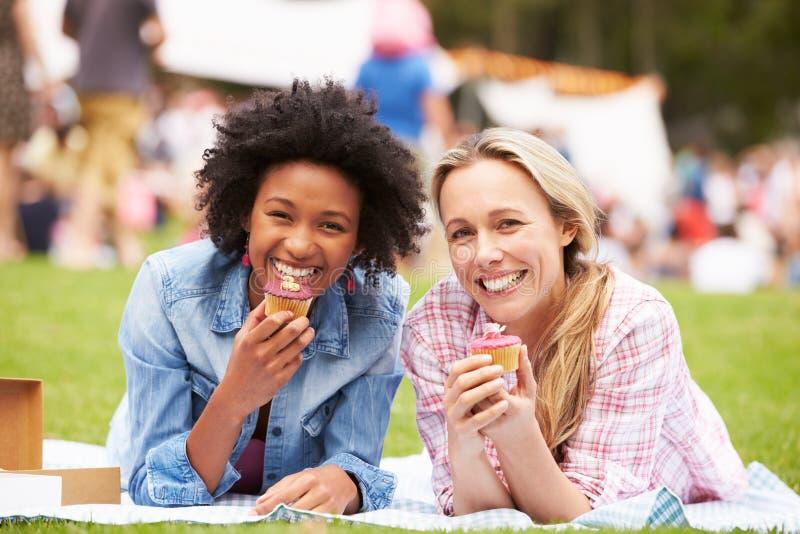 Dos amigos femeninos que gozan de las magdalenas en el evento al aire libre del verano fotos de archivo