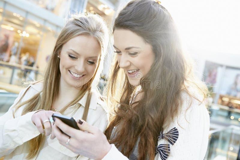 Dos amigos femeninos que hacen compras en la alameda que mira el teléfono móvil imagen de archivo libre de regalías