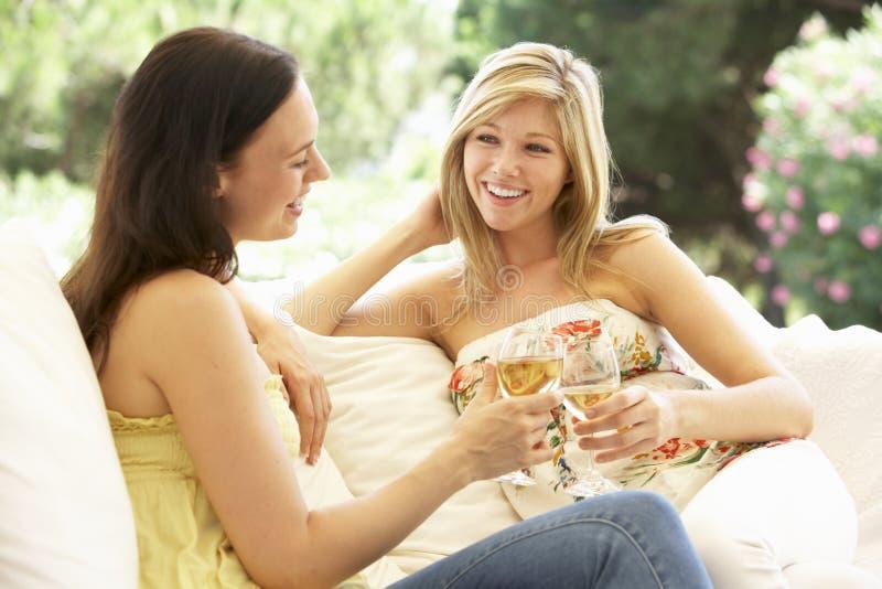 Dos amigos femeninos que se relajan en Sofa With Glass Of Wine foto de archivo