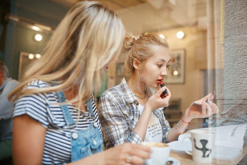 Dos amigos femeninos que se sientan dentro del café que habla y que come el café imagen de archivo