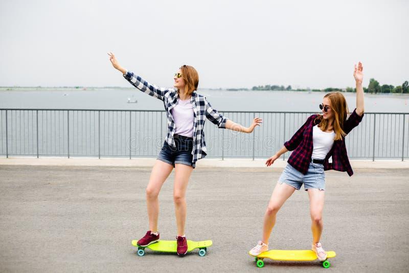 Dos amigos femeninos sonrientes que aprenden longboard que monta con la ayuda Concepto de la amistad fotos de archivo libres de regalías
