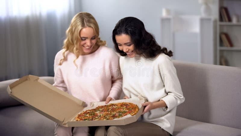 Dos amigos femeninos sonrientes que comen pizza en el lanzamiento, servicio de entrega de la comida fotografía de archivo