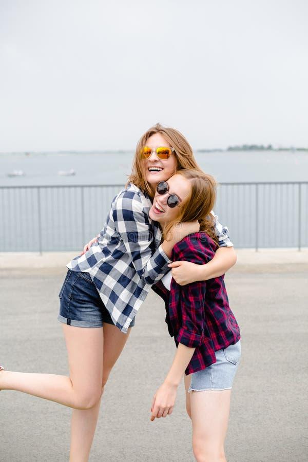Dos amigos femeninos sonrientes que se abrazan en la calle Concepto de los días de fiesta, de las vacaciones, del amor y de la am fotografía de archivo