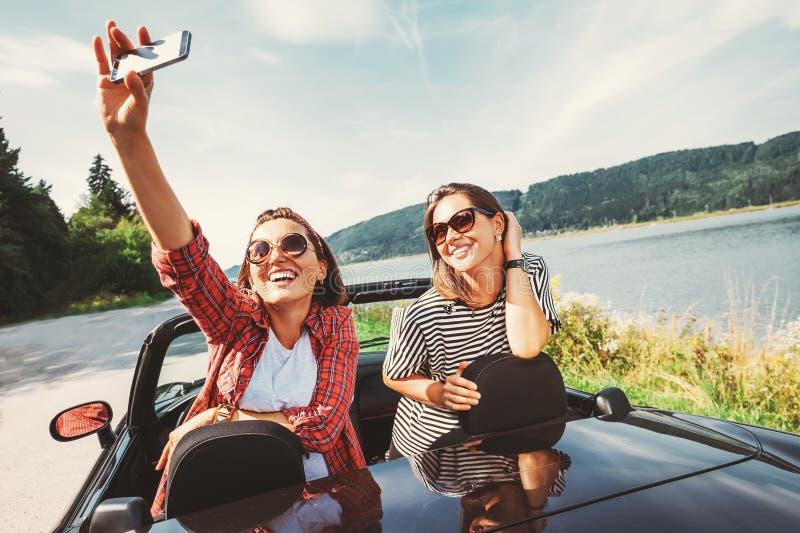 Dos amigos femeninos toman una foto del selfie durante su viaje auto foto de archivo libre de regalías