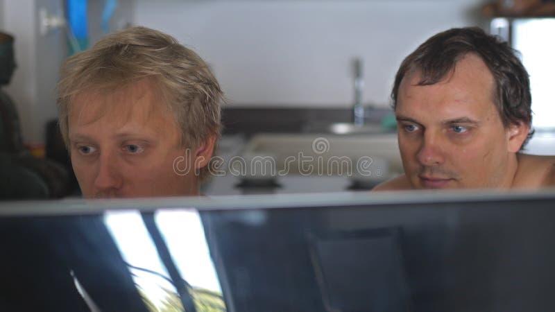 Dos amigos gay de los hombres jovenes con el pecho desnudo en casa que comparte la información y que usa el ordenador Trabajo el  imagen de archivo libre de regalías