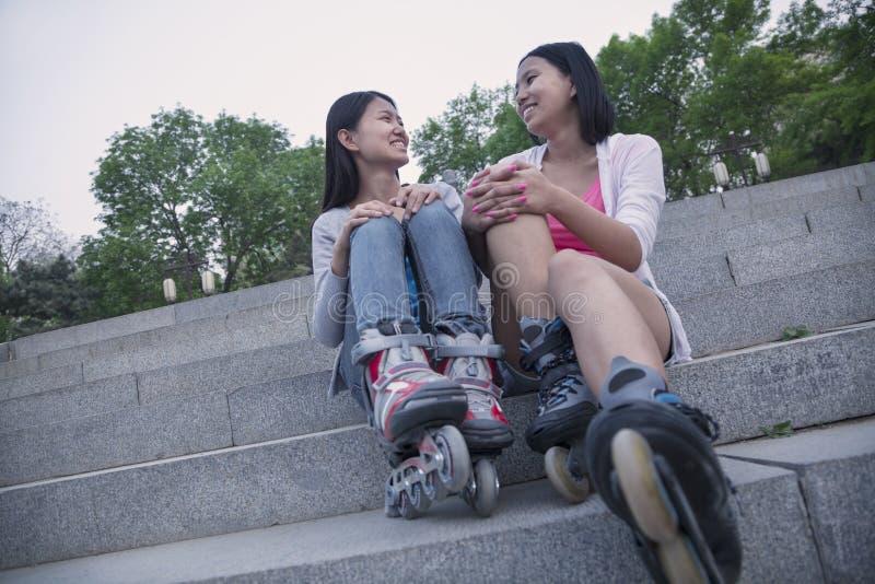 Dos amigos jovenes con las cuchillas del rodillo que se sientan y que descansan sobre pasos concretos al aire libre fotografía de archivo libre de regalías