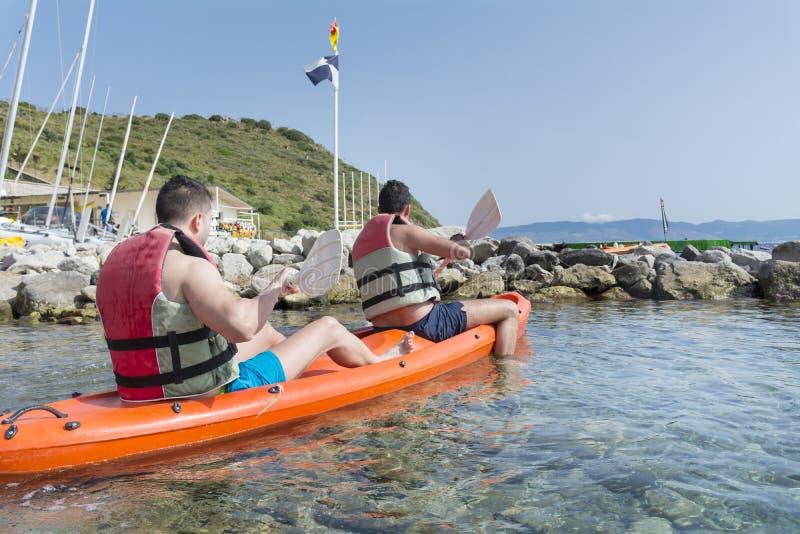 Dos amigos jovenes ejoying las vacaciones, entrando en el mar con la canoa amarilla fotos de archivo
