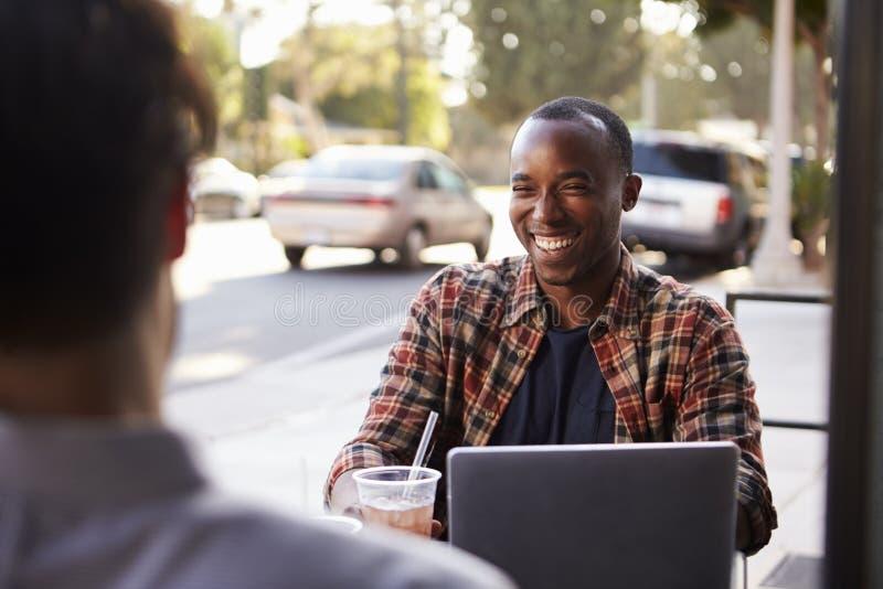 Dos amigos masculinos con las bebidas frías y ordenador portátil fuera del café imagen de archivo