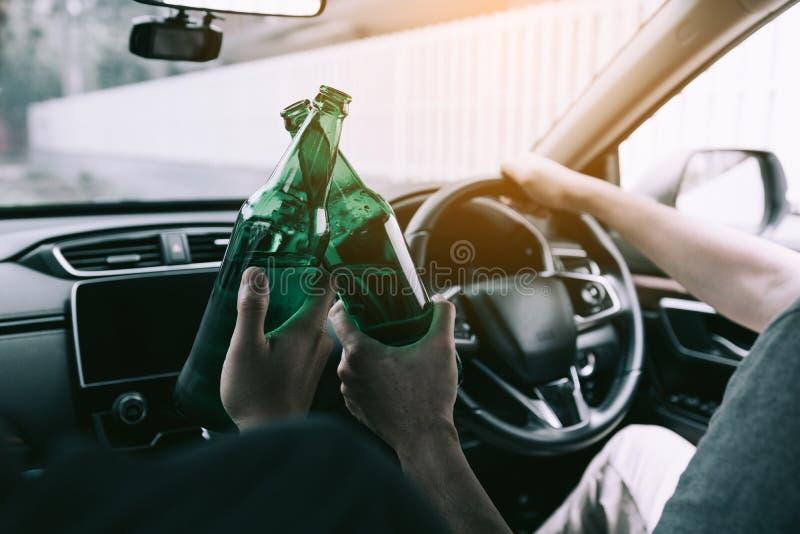 Dos amigos masculinos están celebrando en el coche mientras que están tintineando la botella de cerveza juntos foto de archivo libre de regalías