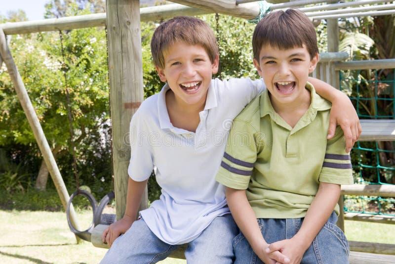 Dos amigos masculinos jovenes en una sonrisa del patio foto de archivo