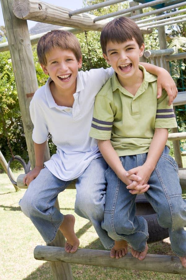 Dos amigos masculinos jovenes en una sonrisa del patio imagen de archivo