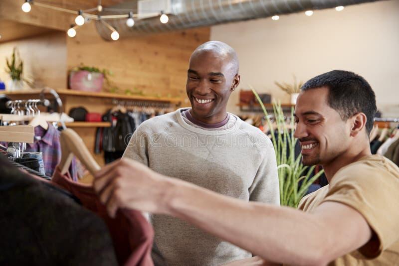 Dos amigos masculinos miran la ropa en una tienda de ropa, cierre para arriba fotos de archivo libres de regalías