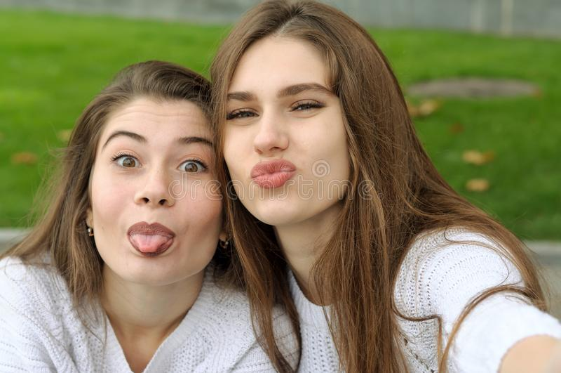 Dos amigos muestran su lengua mientras que hacen una foto del selfie foto de archivo