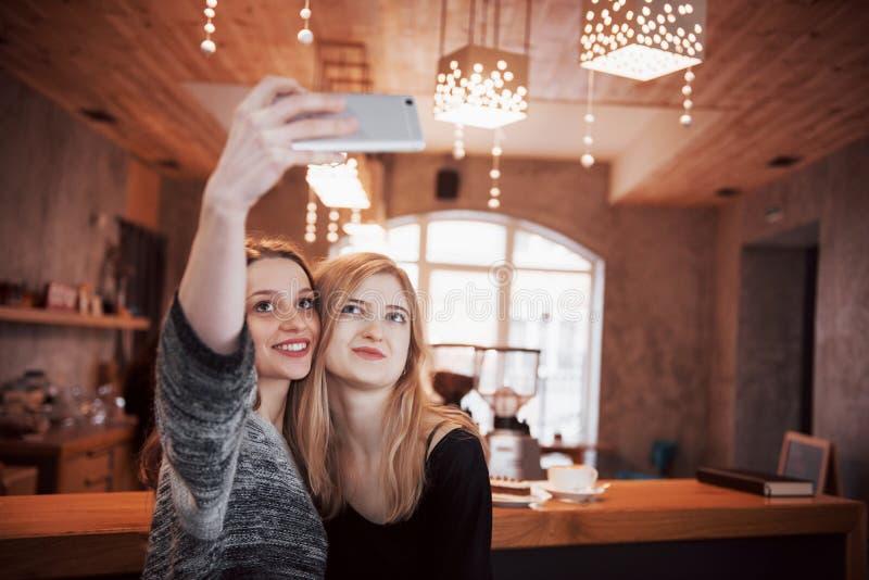 Dos amigos que beben el café en un café, tomando selfies con un teléfono elegante y divirtiéndose que hace caras divertidas Foco  fotos de archivo
