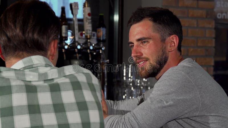 Dos amigos que charlan sobre la cerveza en el pub local fotografía de archivo