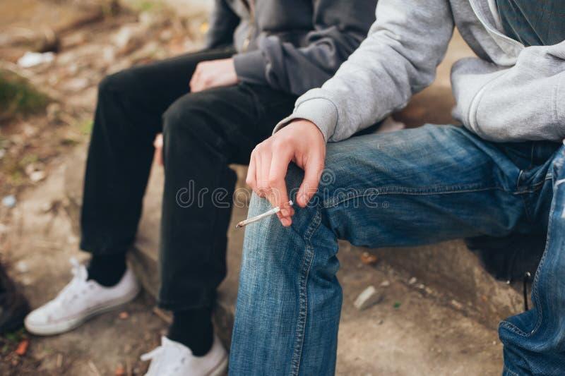 Dos amigos que fuman la junta en la pieza abandonada del ghetto de la ciudad foto de archivo libre de regalías
