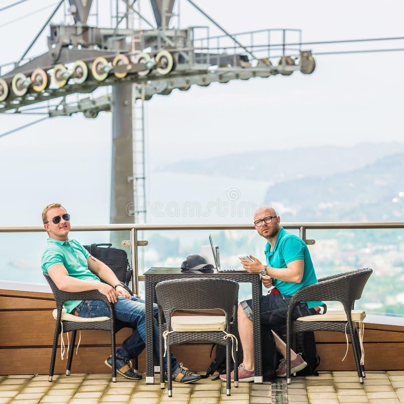 Dos amigos que gozan del café junto afuera imagenes de archivo