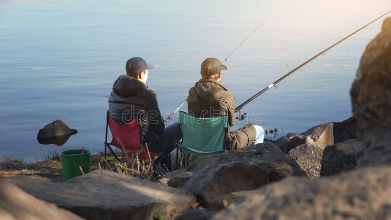 Dos amigos que pescan para escapar la vida de ciudad subrayada, intereses comunes, tiempo libre foto de archivo libre de regalías