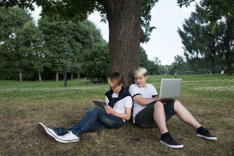 Dos amigos que se sientan en hierba en tableta del parque y ordenador portátil sonrientes y de observaciones Diviértase en línea imagen de archivo libre de regalías