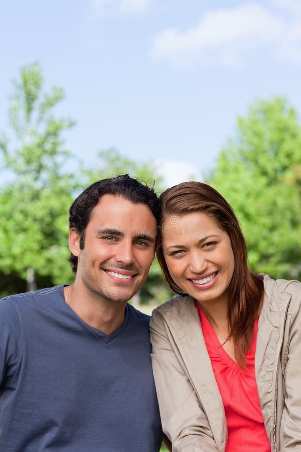 Dos amigos que sonríen como el look ahead mientras que se inclina contra cada uno fotografía de archivo libre de regalías