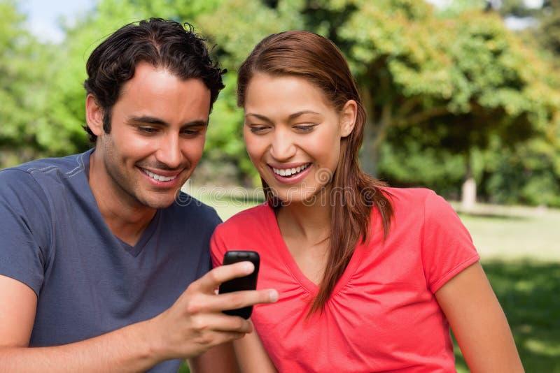 Dos amigos que sonríen como están mirando algo en un móvil fotografía de archivo